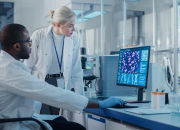Modern Medical Research Laboratory: Two Scientists Use Computer with Screen Showing DNA Gene Analysis, Specialists Discuss Innovative Technology. Advanced Scientific Lab for Medicine, Biotechnology
