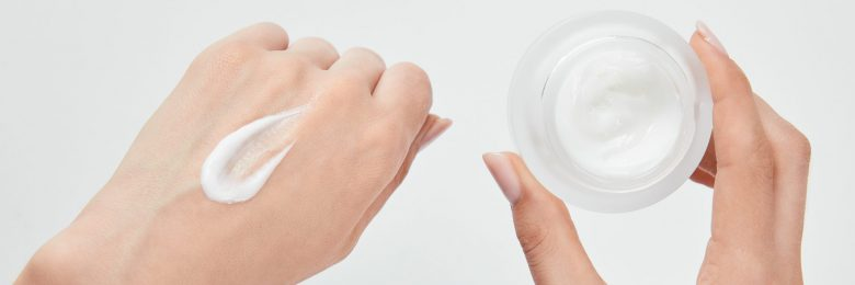 panoramic shot of woman applying cream on skin and holding jar isolated on white